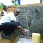 The Water Project: Ikonyero Community, Jesse Spring -  Field Officer Jonathan Mutai Celebrates The New Reservoir Tank