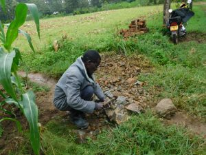 The Water Project:  Community Member Breaking Rocks Into Gravel
