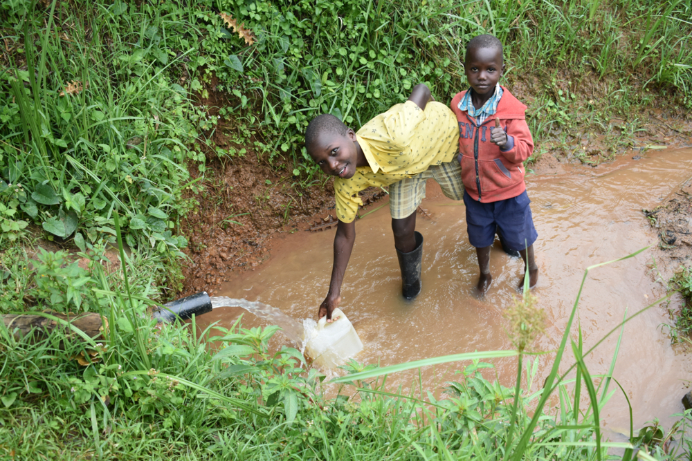 The Water Project : kenya20022-collecting-water-from-shisia-spring-4