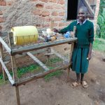 The Water Project: KG Jeptorol Primary School -  Student Choosing A Cup From The Dishrack