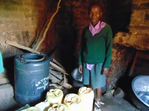 The Water Project:  Pupil Next To Home Water Storage