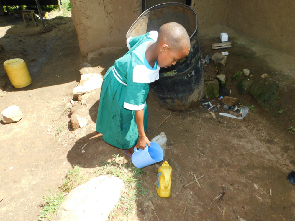 The Water Project : kenya20158-a-girl-fetches-water-at-home