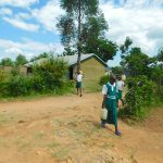 The Water Project: Kitambazi Primary School -  Pupils Arriving With Water From Home
