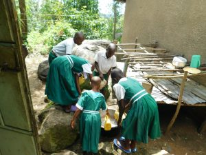 The Water Project:  Students Pour Water Into A Pot For Later Use