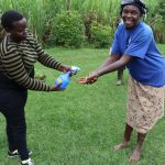 The Water Project: Mahira Community, Wora Spring -  Catherine Sanitizes Participants Hands