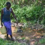 The Water Project: Imbiakalo Community, Askari Spring -  Carrying Water From The Spring