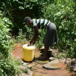 The Water Project: Imbiakalo Community, Askari Spring -  Collecting Water