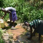 The Water Project: Imbiakalo Community, Askari Spring -  Drawing Water And Rinsing Off Downstream