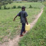 The Water Project: Mukhuyu Community, Gideon Kakai Chelagat Spring -  Stephen Carrying Water Home
