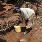 The Water Project: Mukhonje B Community, Peter Yakhama Spring -  Collecting Water