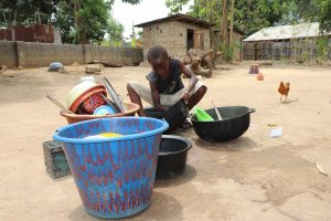 The Water Project:  Small Boy Cleaning Up Dishes