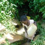 The Water Project: Mushikulu B Community, Olando Spring -  Rinsing Her Container Before Fetching
