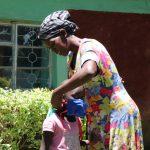 The Water Project: Sharambatsa Community, Mihako Spring -  Helping Her Daughter Put On Her Mask