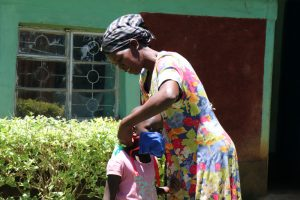 The Water Project:  Helping Her Daughter Put On Her Mask