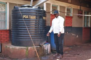 The Water Project:  Pius Airdrying His Hands Next To His Rain Tank