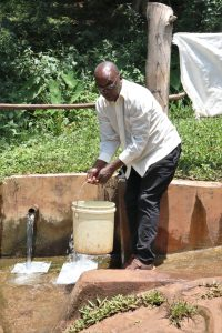 The Water Project:  Pius Taking Water From The Spring