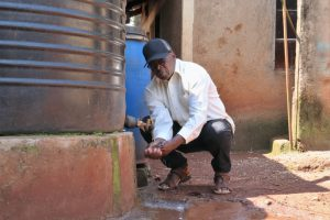 The Water Project:  Pius Washing His Hands At His Home Rain Tank