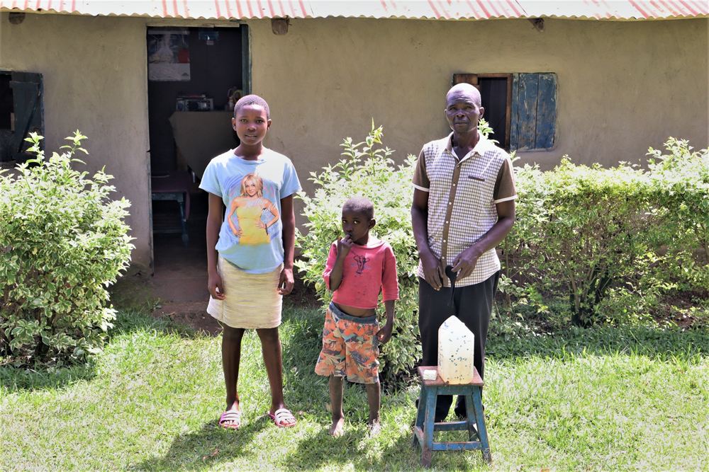 The Water Project : covid19-kenya19145-andrew-with-his-children-in-front-of-their-house