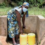 The Water Project: Shitoto Community, Laurence Spring -  Mrs Nashirobe Fetching Water From Laurence Spring