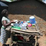 The Water Project: Ematetie Community, Weku Spring -  Getting Plates From The Dishrack To Serve Lunch