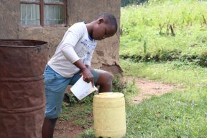 The Water Project:  Joshua Refilling The Handwashing Container