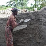The Water Project: Kimuuni Secondary School -  Applying Concrete To The Outside Walls