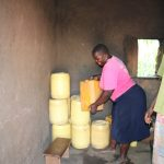 The Water Project: Elwichi Community, Mulunda Spring -  Setting Down Their Containers With Water