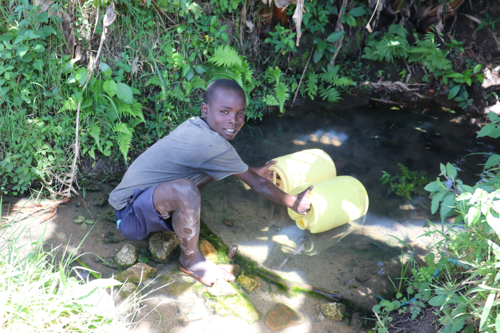 The Water Project : kenya21014-samuel-fetching-water-from-the-spring