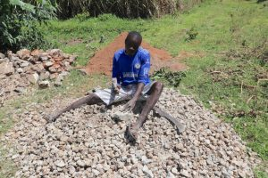 The Water Project:  Titus Splitting Rocks To Gravel