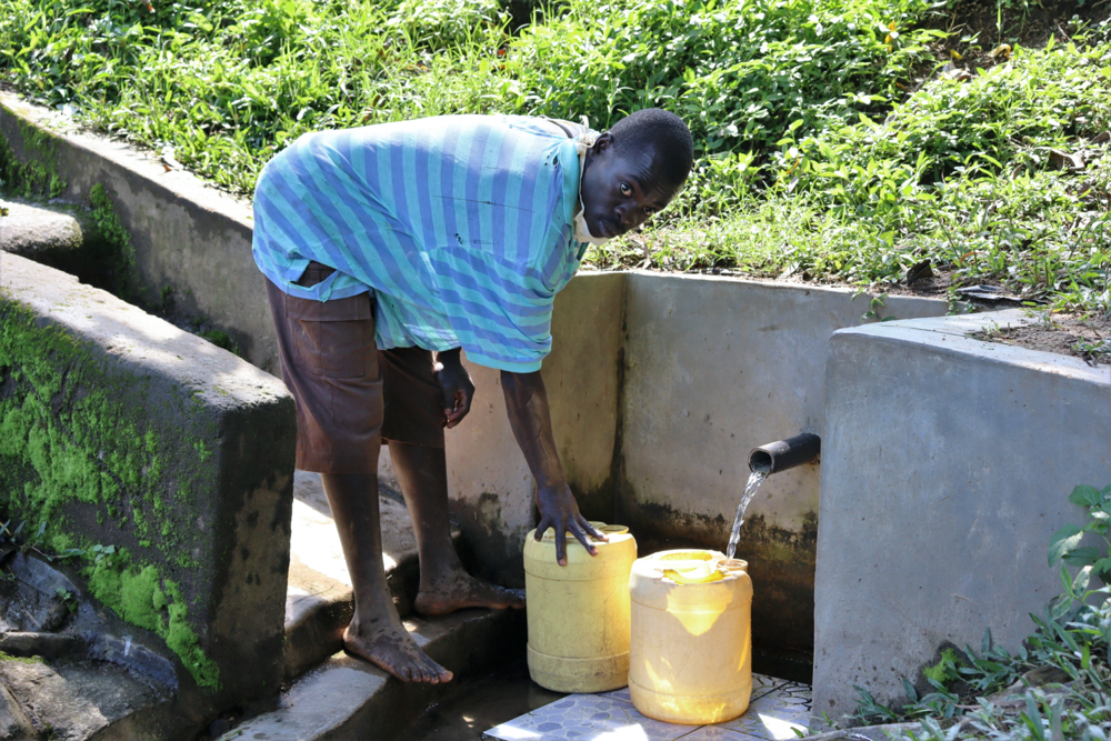 The Water Project : covid19-kenya19120-fetching-water-from-eshiasuli-spring