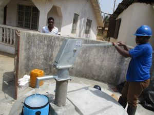 The Water Project:  Staff Collecting Water After Installing Pump