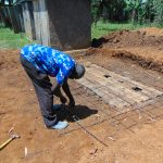 The Water Project: Ivakale Primary School & Community - Rain Tank 2 -  Artisan Moses Obege Setting Latrine Foundation Wire