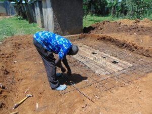 The Water Project:  Artisan Moses Obege Setting Latrine Foundation Wire