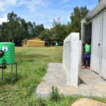 The Water Project: Boyani Primary School -  Pupil Washing Hands At The Latrines