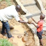 The Water Project: Maraba Community, Nambwaya Spring -  Backfilling With Large Rocks