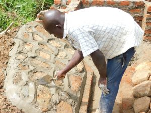 The Water Project:  Plastering The Stone Pitching To Form Rub Wall