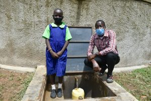 The Water Project:  A Pupil And A Teacher Posing At The Water Tank