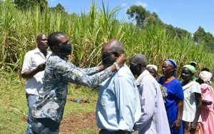 The Water Project:  Area Member Of County Assembly Helps A Man Put On A Mask