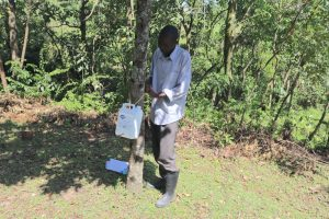 The Water Project:  Tying Leaky Tin On A Tree