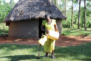 The Water Project:  Refilling Her Handwashing Station With Spring Water