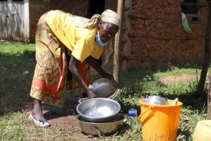 The Water Project:  Ebby Washing Utensils With Tank Water