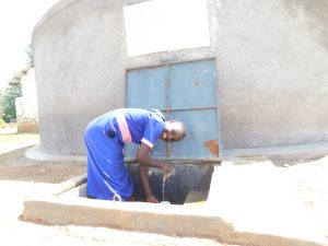 The Water Project:  Irine Gets A Drink From The Rain Tank