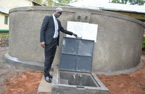 The Water Project:  Principal Posing With The Rain Tank