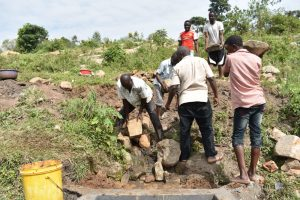 The Water Project:  Community Members Deliver Large Rocks For Backfilling