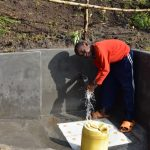 The Water Project: Bukalama Community, Wanzetse Spring -  A Child Washing Hands Before Drinking Water