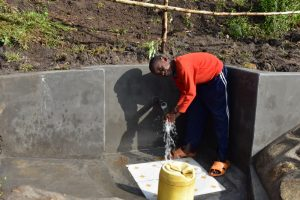 The Water Project:  A Child Washing Hands Before Drinking Water