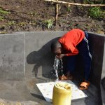 The Water Project: Bukalama Community, Wanzetse Spring -  A Child Drinking Water From The Spring
