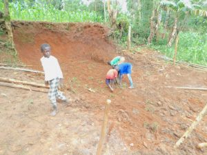The Water Project:  Planting Grass Above Catchment Area