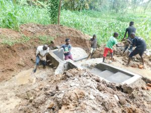 The Water Project:  Teamwork Passing Clay For Backfilling