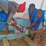 The Water Project: Kamuwongo Primary School -  Kids Drink Water From The Tank